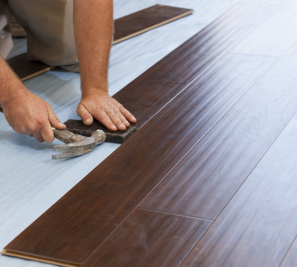 Installing high quality dark wood laminate flooring showing prepared bases.